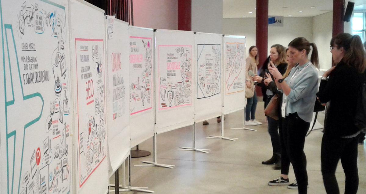 Gäste der OMKB 2018 bewundern die Sketches von Cornelia Koller